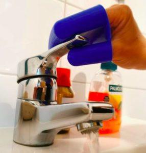 mano con manopla de plástico accionando un grifo evitando el contacto directo
