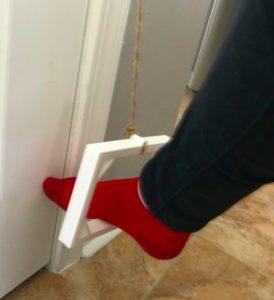 Pie empujando un elemento rectangular sostenido por una cuerda sujeta al pomo para abrir una puerta