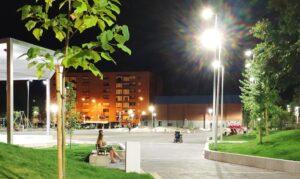 Vista nocturna del acceso a la plaza central del parque.